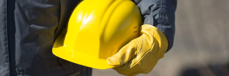 hand of worker with yellow hard-hat,natural light